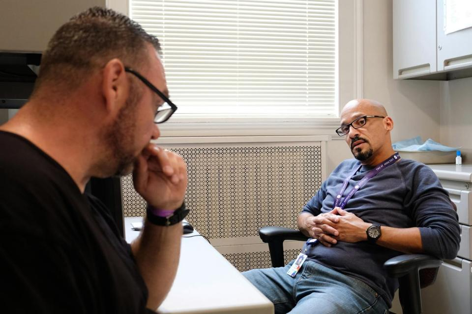 September 30, 2016 - Charlestown, MA Efrain Lozada (right) meets with Brian O'Neill to see how he's doing at Mass General Hospital in Charlestown, MA. Former drug addicts being hired as fulltime employees at Massachusetts General Hospital, one of first hospitals in the country to try this. Kieran Kesner for The Boston Globe.