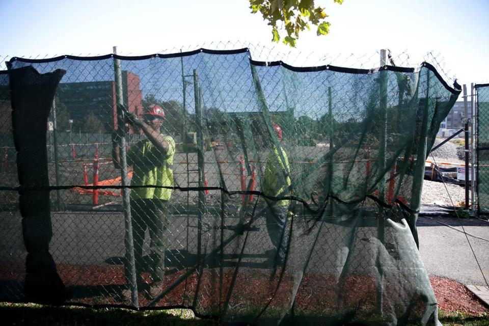 Workers put up a fence at 25 Lewis St., site of the Clipper Ship Wharf project.