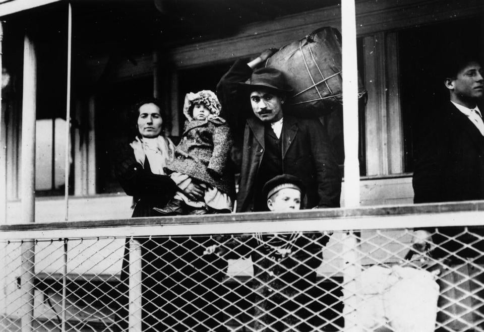 An Italian immigrant family on board a ferry from the docks to Ellis Island, New York. (Photo by Lewis W Hine/Getty Images)
