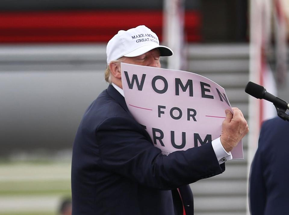 "Republican presidential candidate Donald Trump held a ""Women for Trump"" sign as he spoke during a campaign rally on Wednesday in Lakeland, Fla."