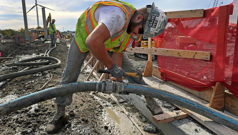 Kevin Rineer working on a cement hose at the construction site of the Wynn Casino in Everett (above).