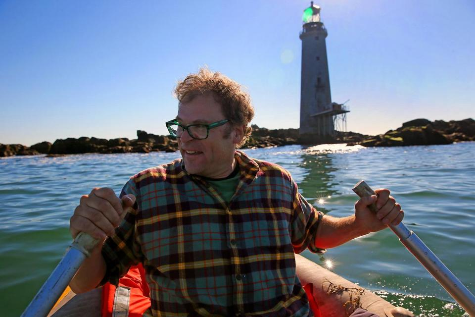 Dave Waller navigates a small dinghy past rocks surrounding the lighthouse he and his wife bought at auction in 2013.