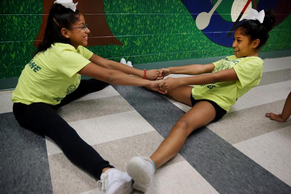 Haylee Obando (left) and her sister Helen, 13, stretched during cheerleader practice.