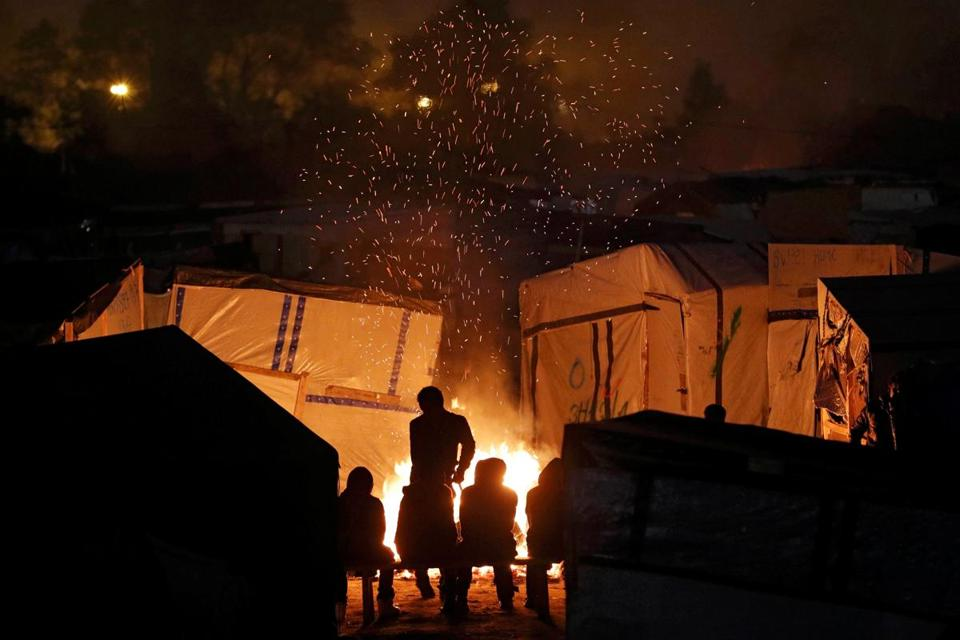 Migrants gathered around a bonfire to warm up in the migrant camp in Calais, France, Monday at sunset.