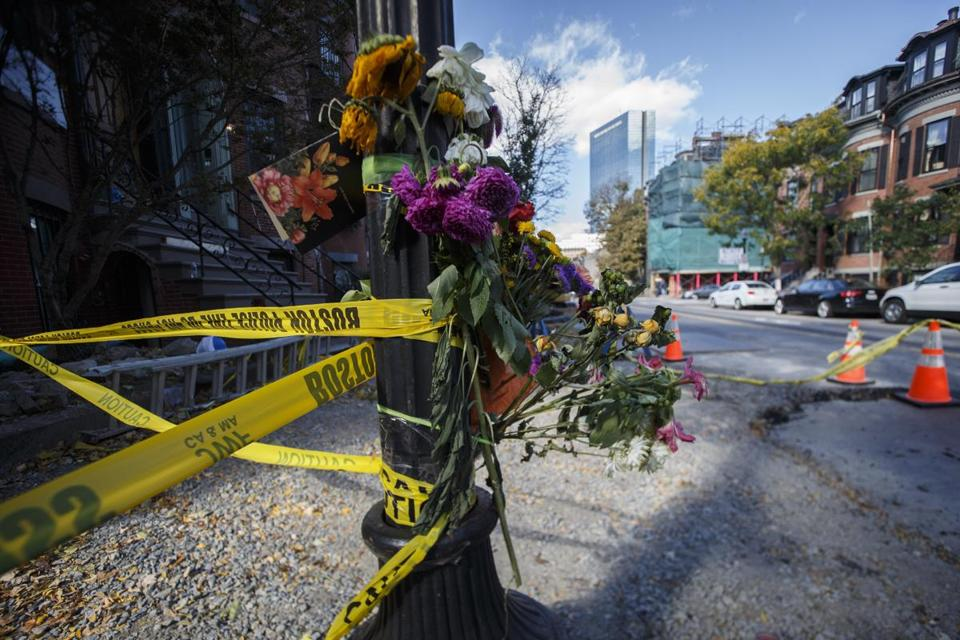 Boston, MA - 10/24/2016 - Flowers hang on a lamp post as a memorial for two construction workers killed at the scene where a water line burst on Dartmouth Street in Boston, MA, October 24, 2016. (Keith Bedford/Globe Staff)