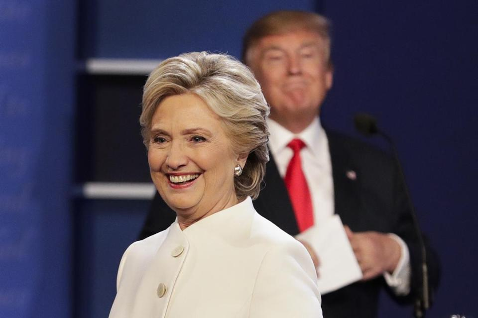 Democratic presidential nominee Hillary Clinton walks off stage as Republican presidential nominee Donald Trump puts his notes away after the third presidential debate at UNLV in Las Vegas, Wednesday, Oct. 19, 2016. (AP Photo/John Locher)