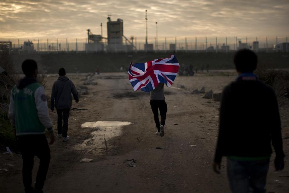 "A man ran with a British flag inside a makeshift camp known as ""the jungle"" near Calais, northern France, on Tuesday."