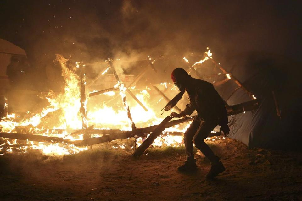 "A migrant watched as a makeshift shelter burned on Tuesday, the second day of the evacuation of the camp known as ""the jungle"" in Calais, France. Authorities are emptying the camp of an estimated 6,300 people and are relocating them around the country."