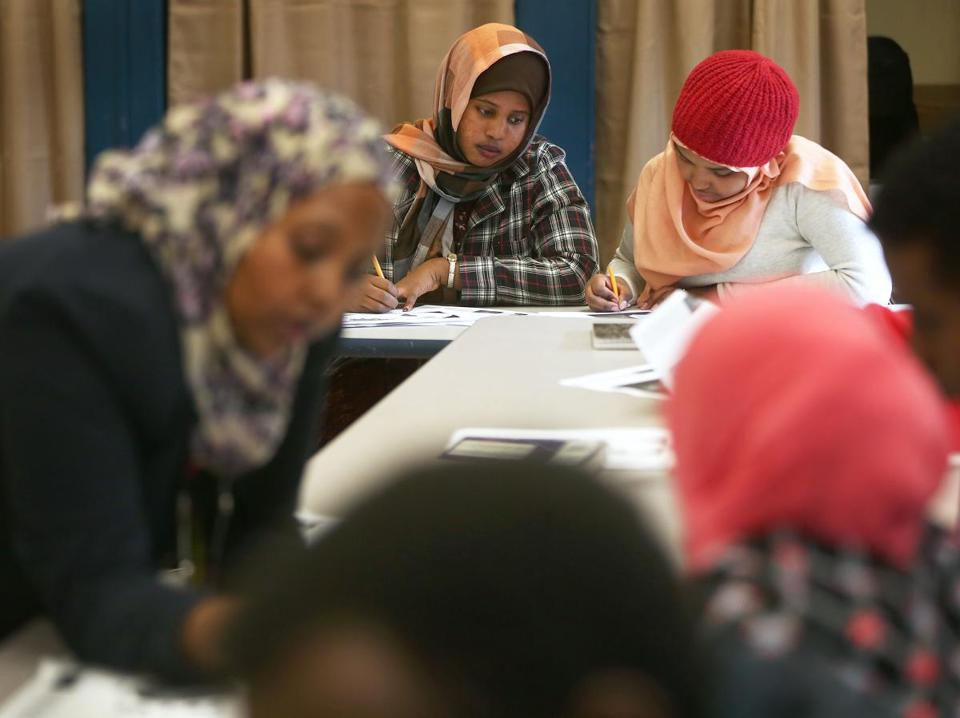 Teacher Mona Farah (left) worked with students at Boston International Newcomers Academy, a district high school that welcomes immigrants who arrive throughout the school year.