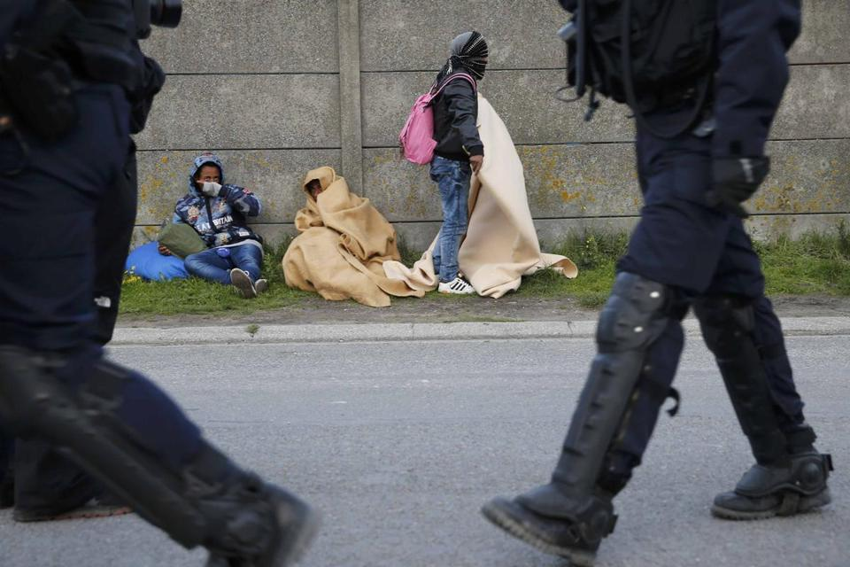 French CRS riot police patrolled near migrants wrapped in blankets in Calais, France, on Thursday.