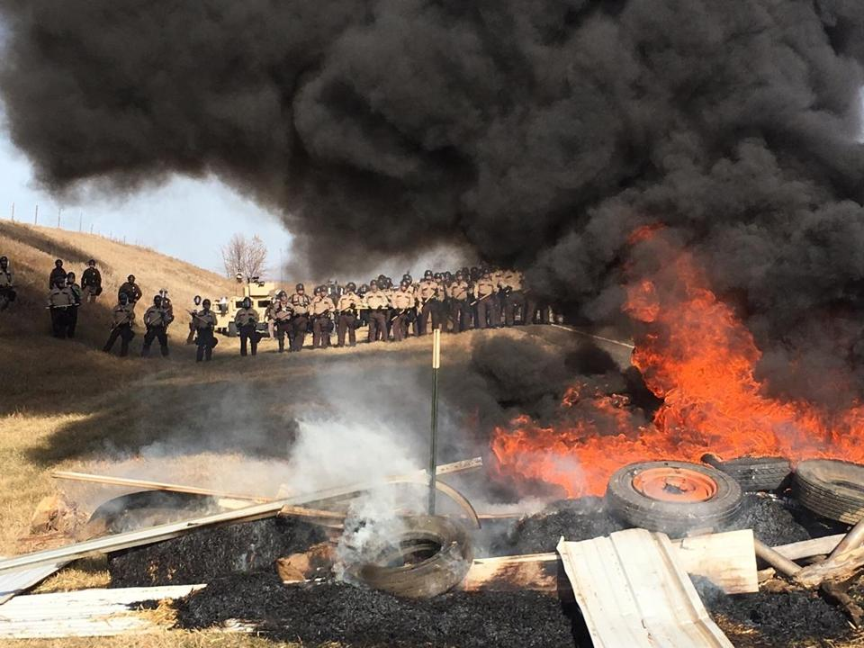 Tires burned as armed soldiers and law enforcement officers lined up on Thursday to force Dakota Access pipeline protesters off private land where they had camped to block construction.