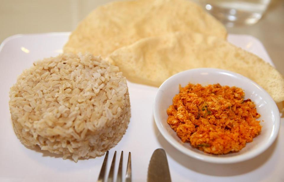 Clockwise from left: Brown rice, pappadums, and coconut sambal.