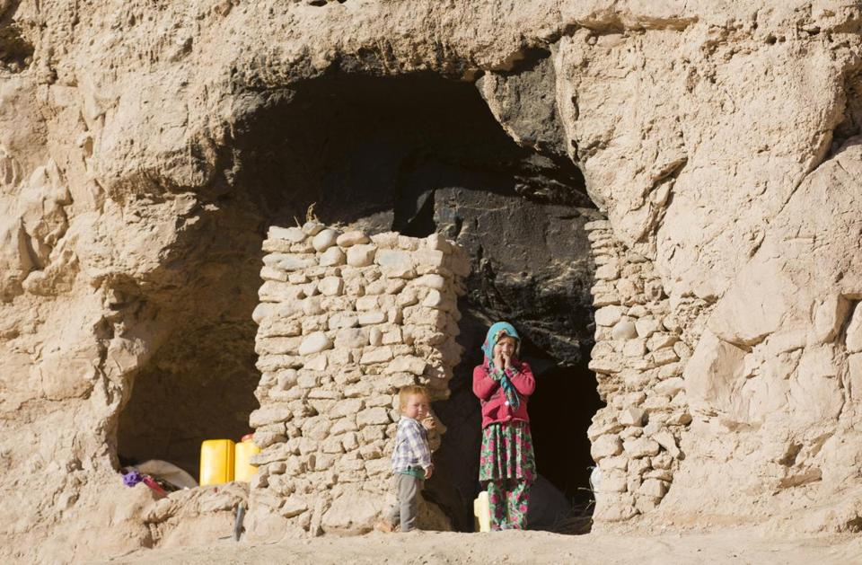 Shepha Qah, 8, and her brother stood by the door of their cave in Bamiyan, Afghanistan.