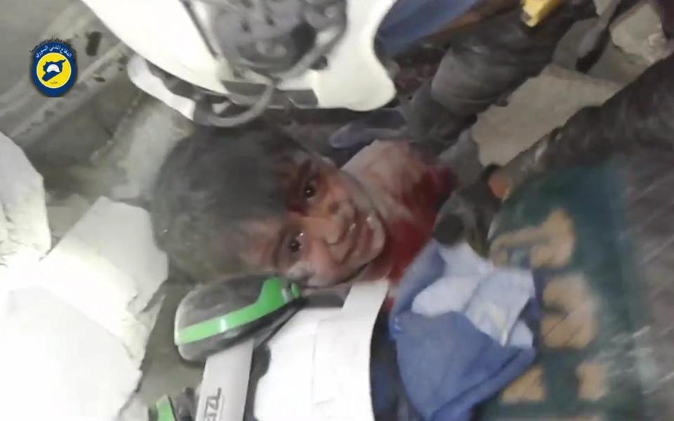 A frame-grab from video footage released on Nov. 17 by the Syrian Civil Defense, also known as the White Helmets, shows rescuers trying to pull out a child trapped under rubble in Aleppo, Syria.