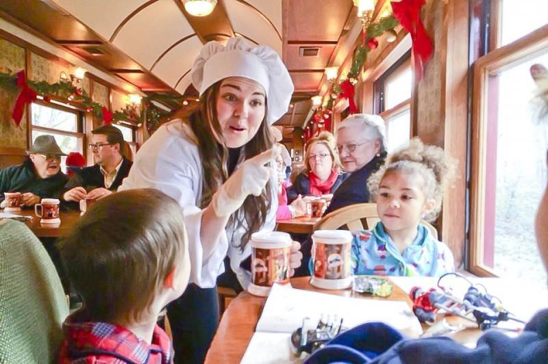 A chef serves hot chocolate to passengers aboard the Polar Express.