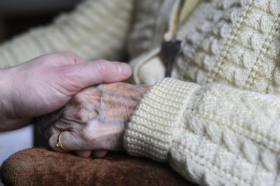 (FILES) This file photo taken on March 18, 2011 shows a woman, suffering from Alzheimer's desease, holding the hand of a relative in a retirement house in Angervilliers, eastern France. For decades now, soaring population growth and ageing rates have been forecast to ignite a global explosion of Alzheimer's, the memory- and freedom-robbing disease afflicting mainly 65-plussers. But an unexpected, and hopeful, trend may be emerging. / AFP PHOTO / Sébastien BOZONSEBASTIEN BOZON/AFP/Getty Images