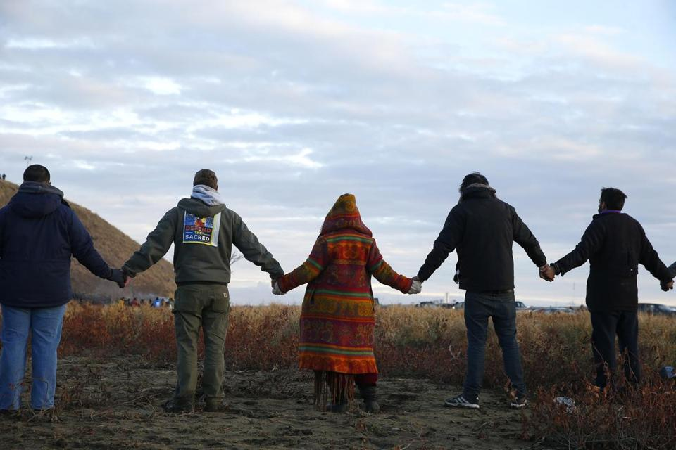 Demonstrators joined hands in prayer at the end of the day's protest at Standing Rock reservation during an ongoing dispute over the building of the Dakota Access Pipeline.