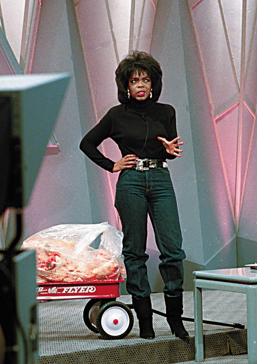 Television talk show host Oprah Winfrey shows off her new figure as she stands in front of 68 pounds of fat inside a toy wagon, in Chicago, Ill, Tuesday, Nov. 16, 1988. Winfrey credited her 68-pound weight loss to a liquid diet and excercise. Her goal was to fit into a size 10 pair of blue jeans for the first time on her syndicated TV show. (AP Photo/Charles Bennet)