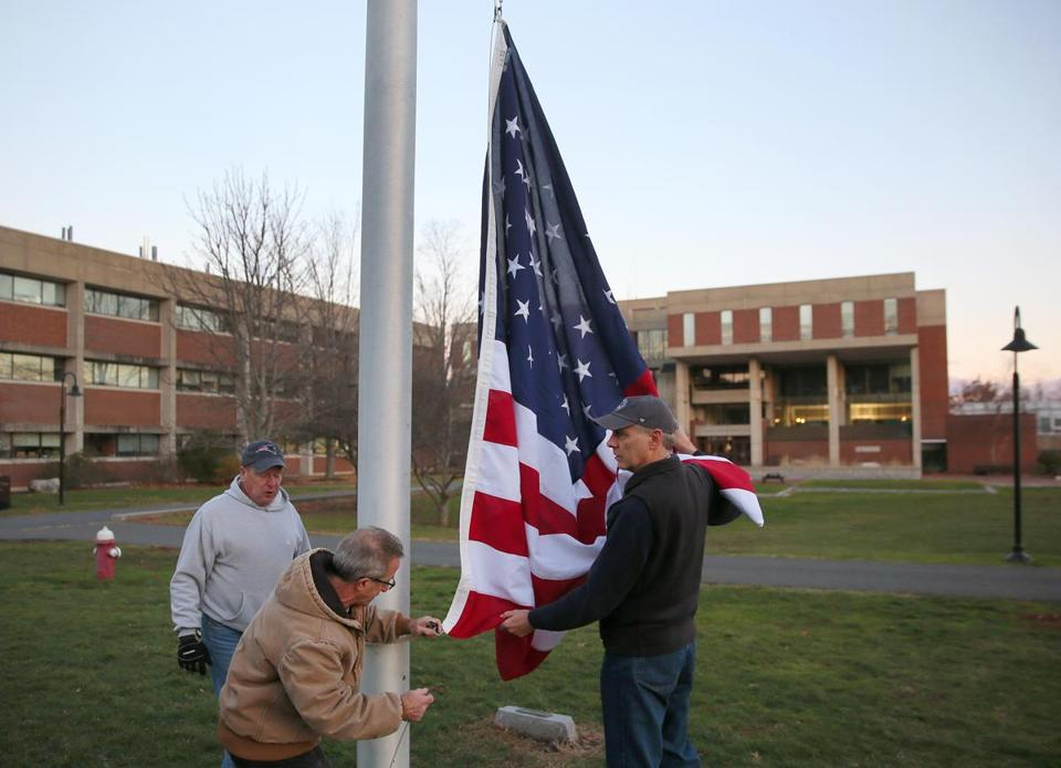 AMHERST, MA - 12/02/2016:Flag is raised early this morning on the Hampshire College campus by L-R Ed Kapinos ( cq) , Bill Kalmakis(cq) and Carl Weber (cq) (David L Ryan/Globe Staff Photo) SECTION: METRO TOPIC 03hampshire
