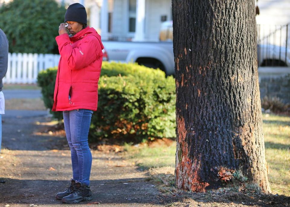 An emotional Regina Lewis stood near the tree on Brush Hill Road where the youngest of her six children died in a fiery car crash early Friday.