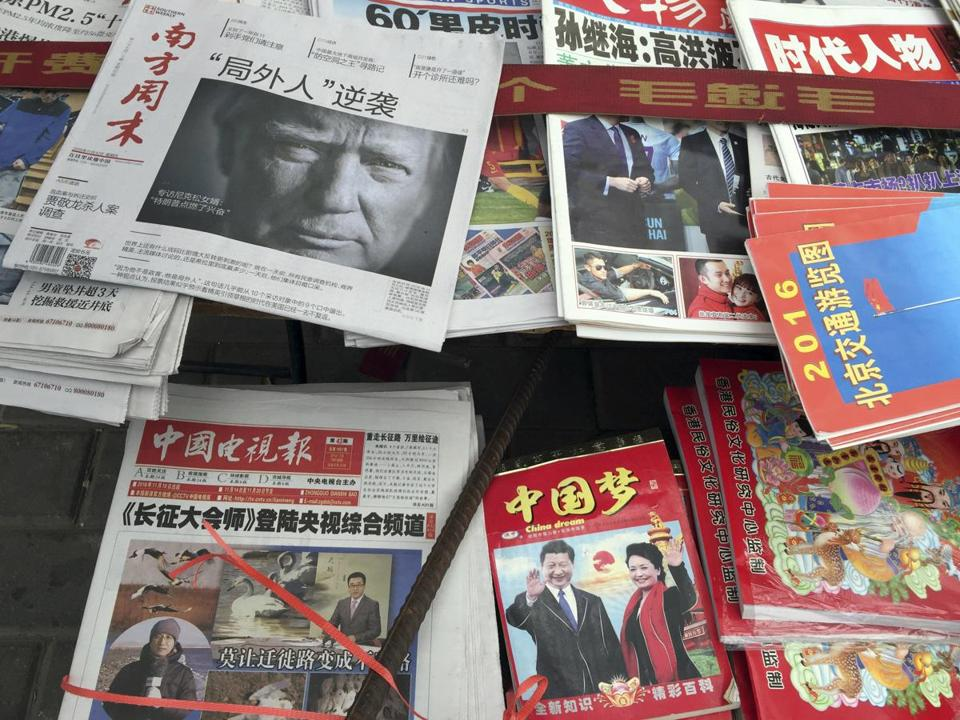 "FILE - In this Nov. 10, 2016 file photo, a front page of a Chinese newspaper with a photo of U.S. President-elect Donald Trump and the headline ""Outsider counter attack"" is displayed at a newsstand in Beijing, China. With Trump's latest tweets touching on sensitive issues, China must decide how to handle an incoming American president who relishes confrontation and whose online statements appear to foreshadow shifts in foreign policy. China awoke Monday, Dec. 5, to criticism from Trump on Twitter, days after it responded to his telephone conversation with Taiwan's president by accusing the Taiwanese of playing a ""little trick"" on Trump. (AP Photo/Ng Han Guan)"