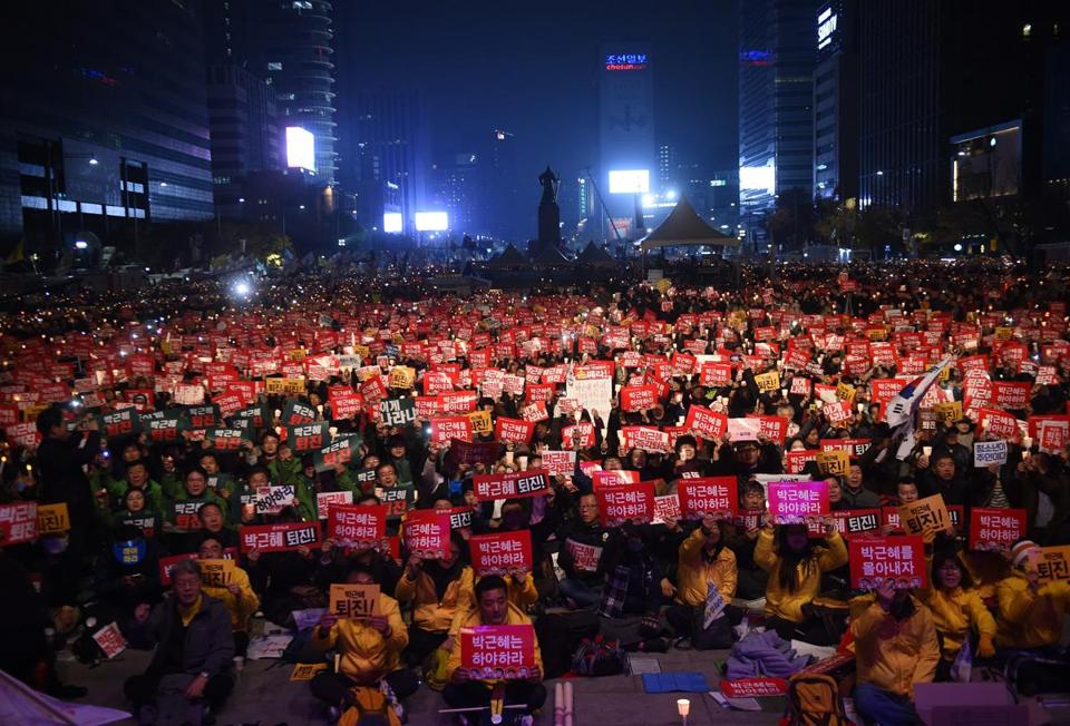 TOPSHOT - Protesters hold candles and banners calling for the resignation of South Korea's President Park Geun-Hye during an anti-government rally in central Seoul on November 19, 2016. Tens of thousands of protestors rallied in Seoul on November 19, for the fourth in a weekly series of mass protests urging President Park Geun-Hye to resign over a corruption scandal. / AFP / JUNG YEON-JE (Photo credit should read JUNG YEON-JE/AFP/Getty Images)