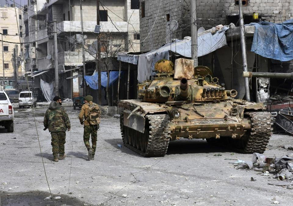 In this photo released by the Syrian official news agency SANA, two Syrian soldiers pass by a tank where government forces have captured wide areas in eastern Aleppo, Syria, Monday, Dec. 12, 2016. Syria's military said Monday it has regained control of 98 percent of eastern Aleppo, as government forces close in the last remaining sliver of a rebel enclave packed with fighters as well as tens of thousands of civilians. (SANA via AP)