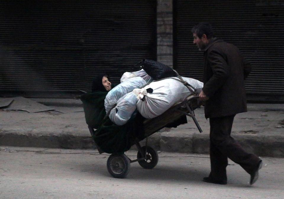 Syrian civilians flee the Aleppo's Sukkari neighborhood on Monday. Large areas of Aleppo and other cities and towns in Syria have been reduced to rubble by the five-year civil war.