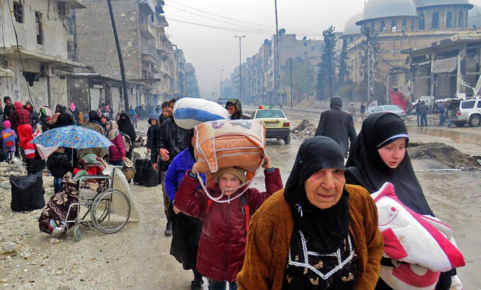 Syrian residents, fleeing violence elsewhere in Aleppo, arrive in the city's Fardos neighborhood Tuesday.