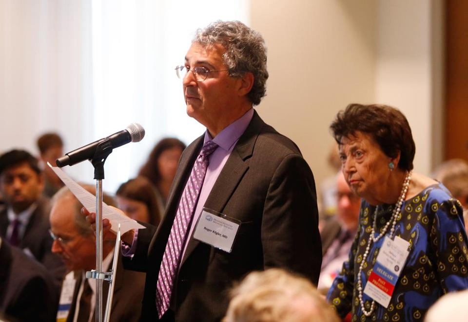 "Dr. Roger Kligler, who has metastatic prostate cancer, spoke to the Massachusetts Medical Society in support of what he calls ""medical aid in dying."" Standing behind him waiting to speak was Dr. Barbara Rockett, a former two-time president of the medical society who opposes this end-of-life option and calls it ""physician-assisted suicide."""
