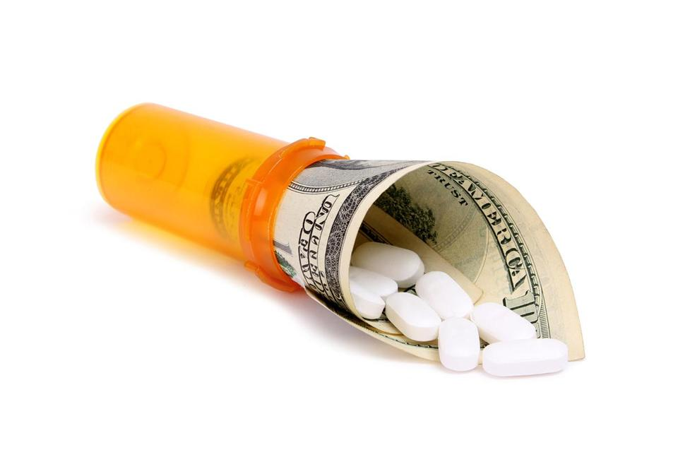 bottle of pills and money isolater on white; Shutterstock ID 113795932; PO: oped