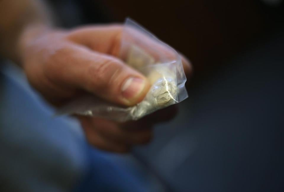 A police officer holds a bag of heroin confiscated as evidence, in Gloucester,  March 2016.