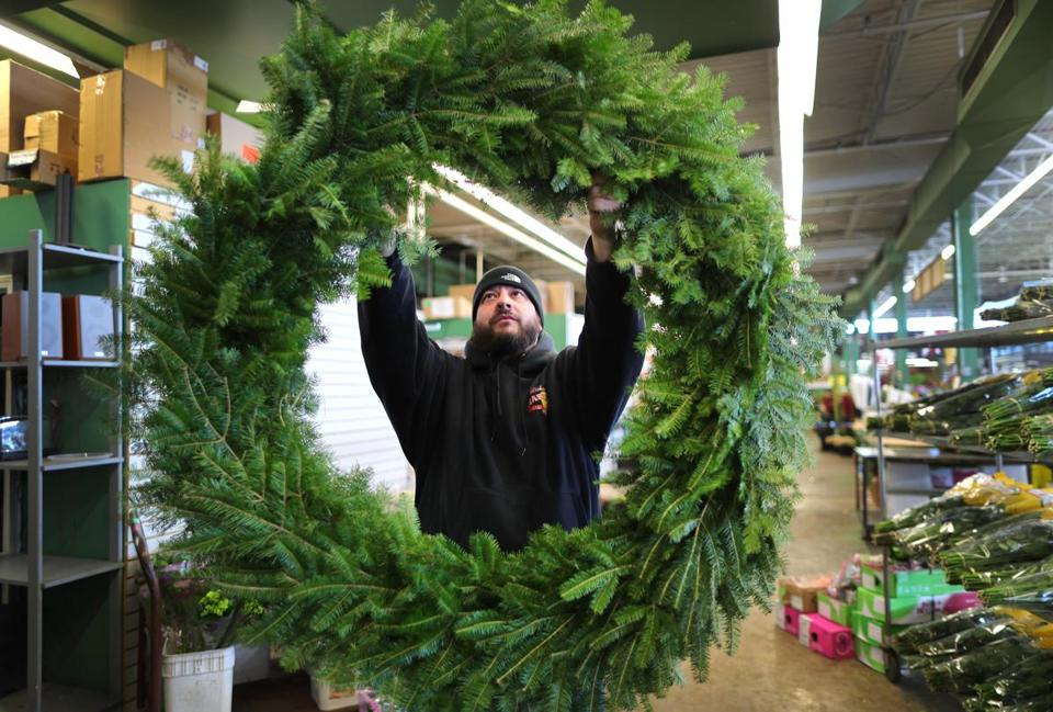Boston-12/16/2016- The Boston Flower Exchange is in it's last days at their location at 540 Albany Street before closing. Most vendors will move to Chelsea in February. Marc Masucci displays a 4 foot wide holiday wreath for a customer at R.J. Carbone. John Tlumacki/Globe Staff (business)