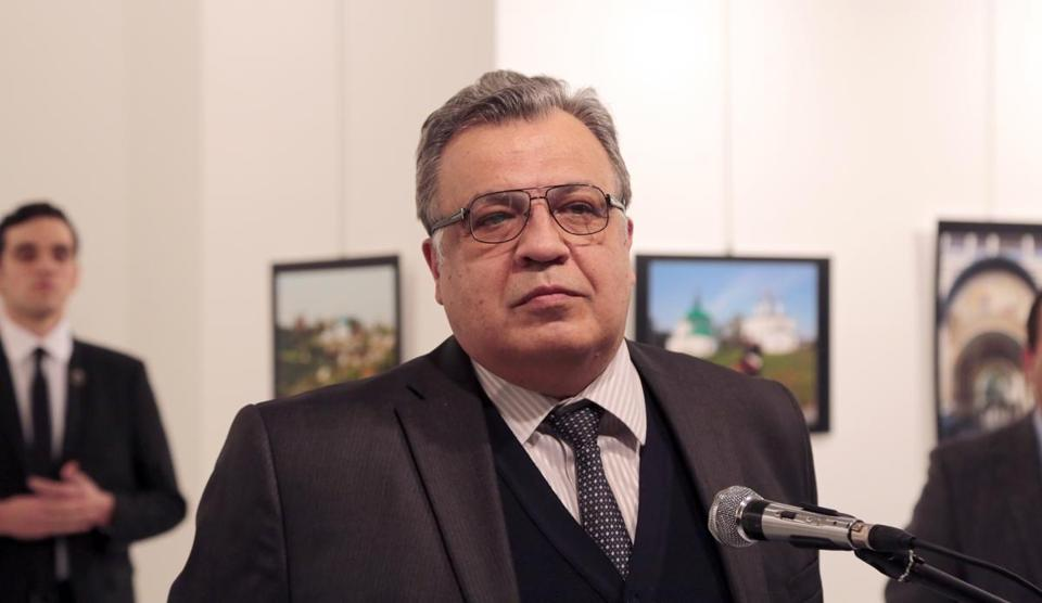 At left, the alleged gunman that assassinated Russian ambassador Andrei Karlov stood behind the diplomat during the opening minutes of his speech.