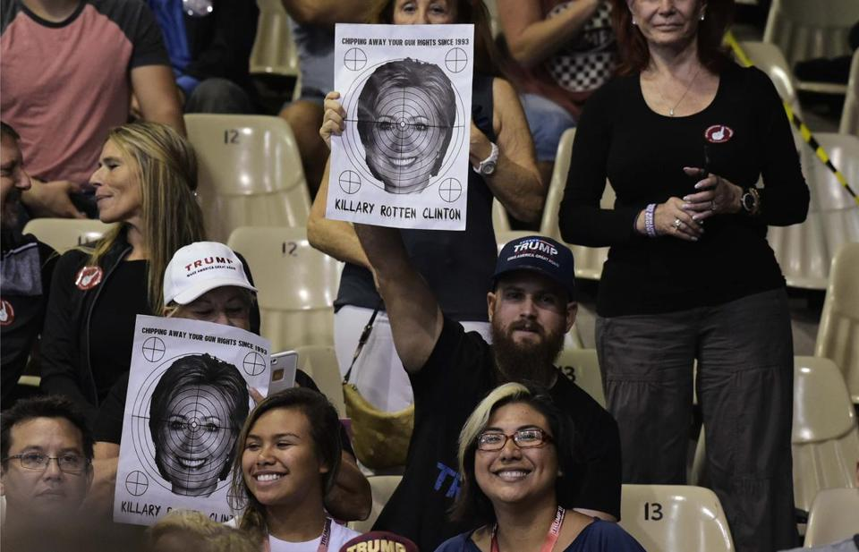 Supporters hold a poster of Hillary Clinton with a target over it at a rally for Republican presidential nominee Donald Trump in the Robarts Arena of the Sarasota Fairgrounds on November 7, 2016 in Sarasota, Florida. Hillary Clinton and Donald Trump launched into the frenzied final day of their historic fight for the White House Monday, with blow-out rallies in the handful of swing states that will decide who leads the United States. / AFP / MANDEL NGAN (Photo credit should read MANDEL NGAN/AFP/Getty Images)