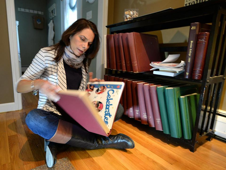 "Cohasset 12/19/2016 : Personal organizer, Lisa Dooley from ""Your Organized Life"" in Cohasset, looks through one of the many organized albums that are filled with pictures and memorabilia. Photo by Debee Tlumacki for the Boston Globe (south)"