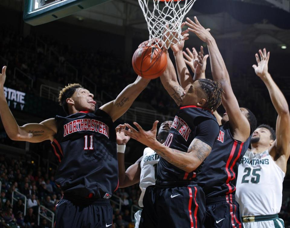 Northeastern's Jeremy Miller (11) is in position for the rebound in the Huskies' win at Michigan State Sunday.