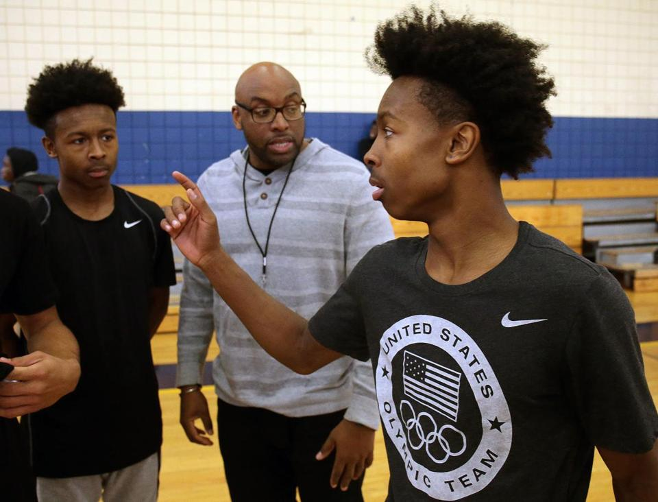 Hyde Park, MA - 12/20/2016 - High school boys' basketball feature - L to R: Charles and Charlie Mitchell, senior twins who form the starting backcourt for the New Mission boys' basketball team with head coach Cory McCarthy during a recent practice. - (Barry Chin/Globe Staff), Section: Sports, Reporter: Owen Pence, Topic: 22schtwins, LOID: 8.3.1059591314.