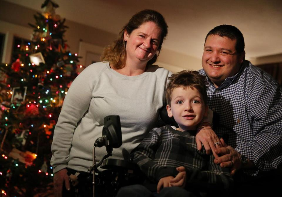 Seven-year-old Matthew Davidopoulos, who has spinal muscular atrophy, posed for a portrait with his parents Courtney and Paul at their home in Westford.