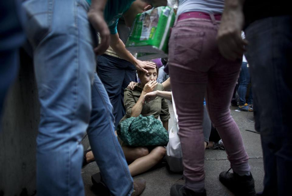 FILE - In this May 5, 2016 file photo, Irama Carrero is aided by fellow shoppers after fainting in a food line outside a grocery store, in Caracas, Venezuela. Carrero, who said she hadn't eaten that day, had spent hours staring blankly ahead in the line for the elderly when her gaze suddenly became more fixed. She tilted backward and no one broke her fall. Her head smacked the concrete and when she came to she started vomiting. (AP Photo/Ariana Cubillos, File)