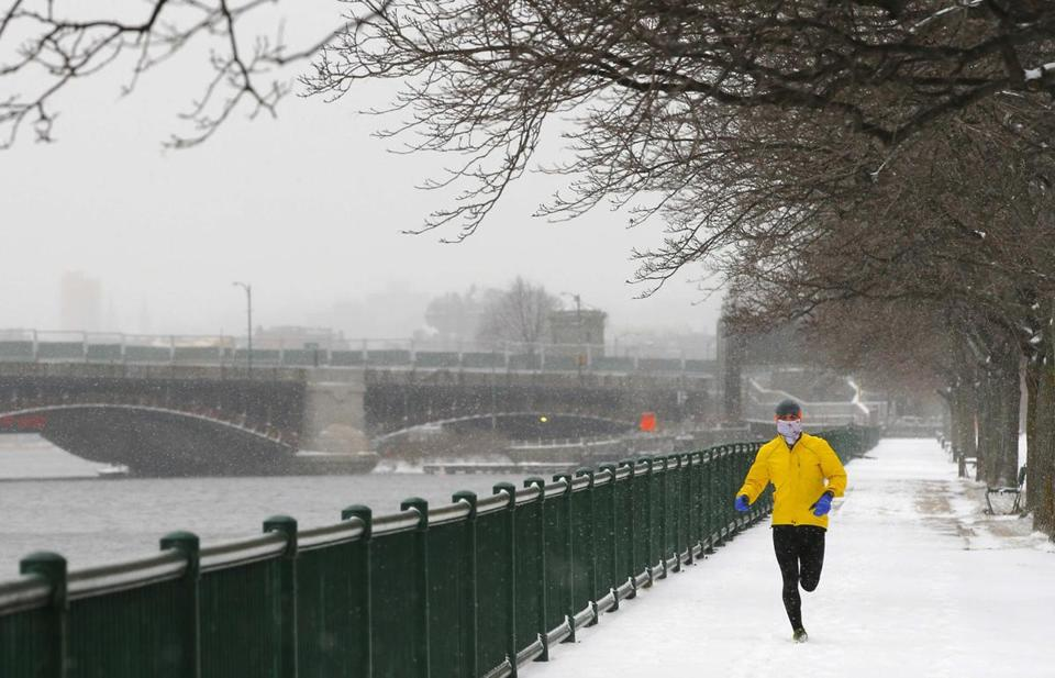 A runner braves falling snow along the Charles River in Cambridge.