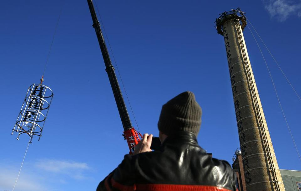 "Jamaica Plain, MA -- 12/28/2016 - Robert Maloney, the Jamaica Plain based artist who designed the crown watches as his big stainless steel creation is raised to go atop the Haffenreffer smokestack. ""It's just incredible. "" Maloney said, ""I've been plugging away at this for years and just to see it in the flesh, in the steel, is amazing."" (Jessica Rinaldi/Globe Staff) Topic: 28brewery Reporter:"