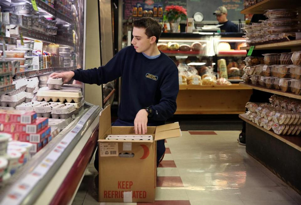 Part-time employee Sam Deeb, 18, stocked eggs in a cooler at Winthrop Marketplace.