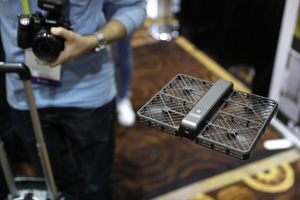 The Hover Camera Passport flies during CES Unveiled before CES International, Tuesday, Jan. 3, 2017, in Las Vegas. The drone uses facial recognition software to automatically follow the user around and shoot video. (AP Photo/John Locher)