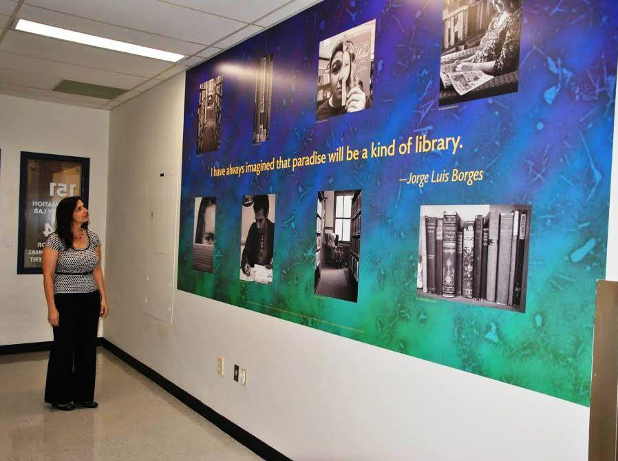 "Northern Essex Community College Lawrence Librarian Jennifer Fielding looks at ""The Library"" mural that was installed outside the information literacy lab in the Dimitry Building."