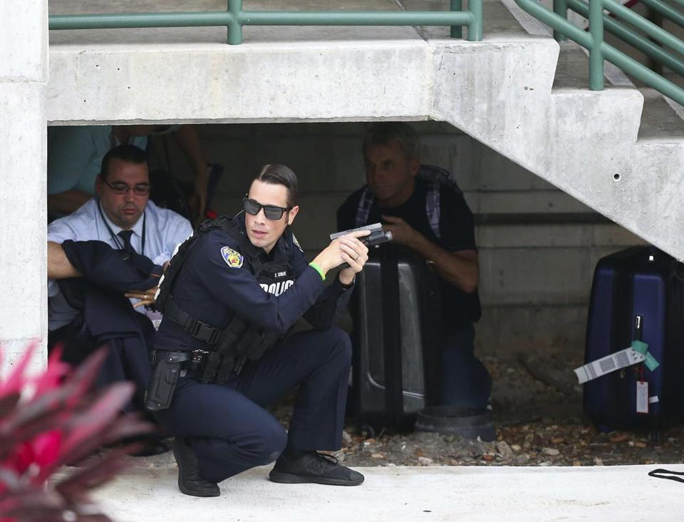 Law enforcement personnel shield civilians outside a garage area at Fort Lauderdale–Hollywood International Airport, Friday, Jan. 6, 2017, in Fort Lauderdale, Fla., after a shooter opened fire inside a terminal of the airport, killing several people and wounding others before being taken into custody. (David Santiago/El Nuevo Herald via AP)