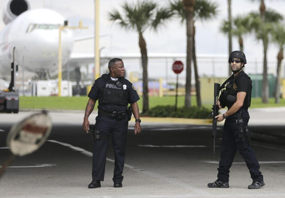 Police officers stand on the perimeter road along the Fort Lauderdale-Hollywood International Airport after a shooter opened fire inside a terminal of the airport, killing several people and wounding others being taken into custody, Friday, Jan. 6, 2017, in Fort Lauderdale, Fla. AP Photo/Lynne Sladky)