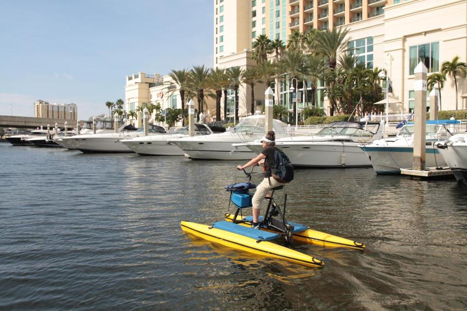 A water bike rider follows the Tampa Riverwalk along Garrison Channel.