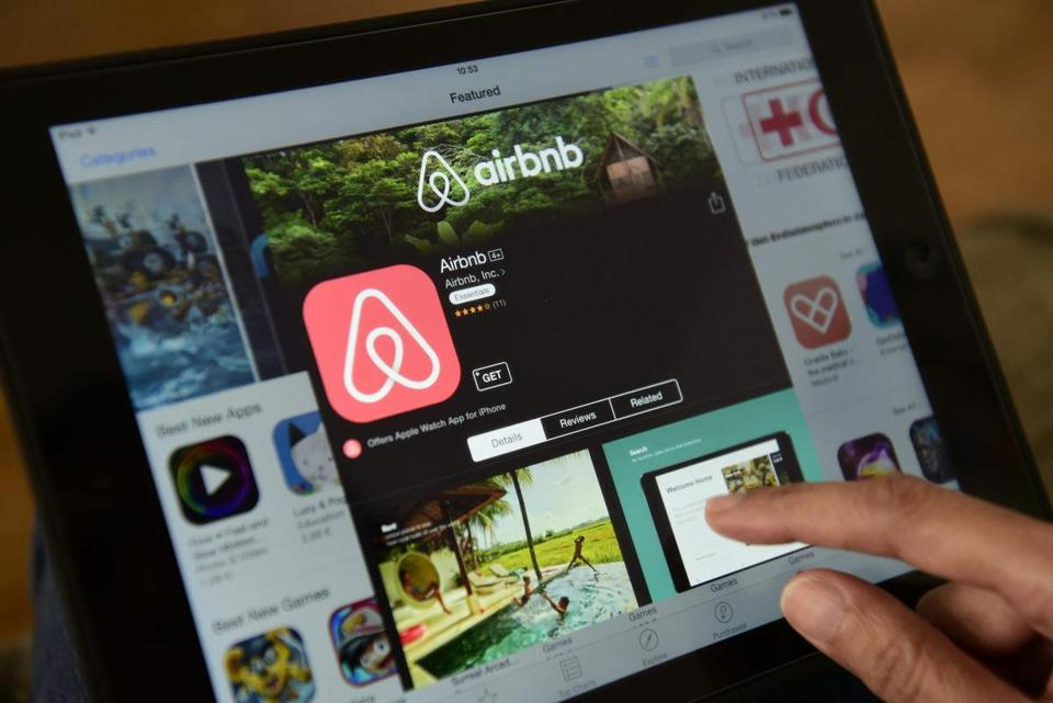 (FILES) This file photo taken on April 28, 2016 shows a woman browsing the site of US home sharing giant Airbnb on a tablet in Berlin on April 28, 2016. Barcelona city hall said on November 24, 2016 it would fine home rental websites Airbnb and rival HomeAway 600,000 euros ($635,000) each for marketing lodgings that lacked permits to host tourists. The fine comes as the popular seaside resort struggles with a rising tide of tourism that has exasperated locals, threatening to drive out poorer residents and spoil the charm of Spain's second-largest city. / AFP PHOTO / John MACDOUGALLJOHN MACDOUGALL/AFP/Getty Images