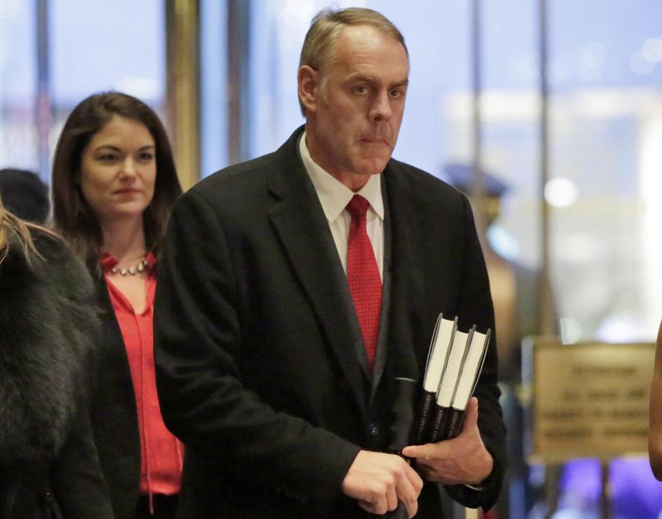 FILE - In this Dec. 12, 2016, file photo, Interior Secretary-designate Rep. Ryan Zinke, right, R-Mont., arrives in Trump Tower, in New York, Monday, Dec. 12, 2016. Zinke says he would never sell, give away or transfer public lands, a crucial stance in his home state of Montana and the West, where access to hunting and fishing is considered sacrosanct. (AP Photo/Richard Drew, File)